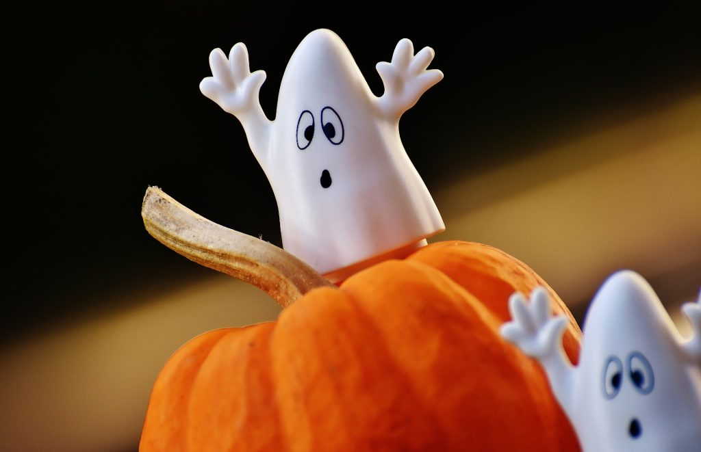 Picture of a cute toy ghost standing on top of a pumpkin.