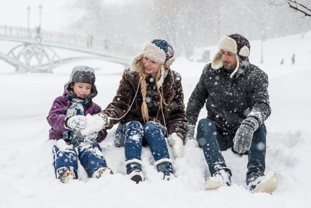 Picture of a family happily sitting in snow.