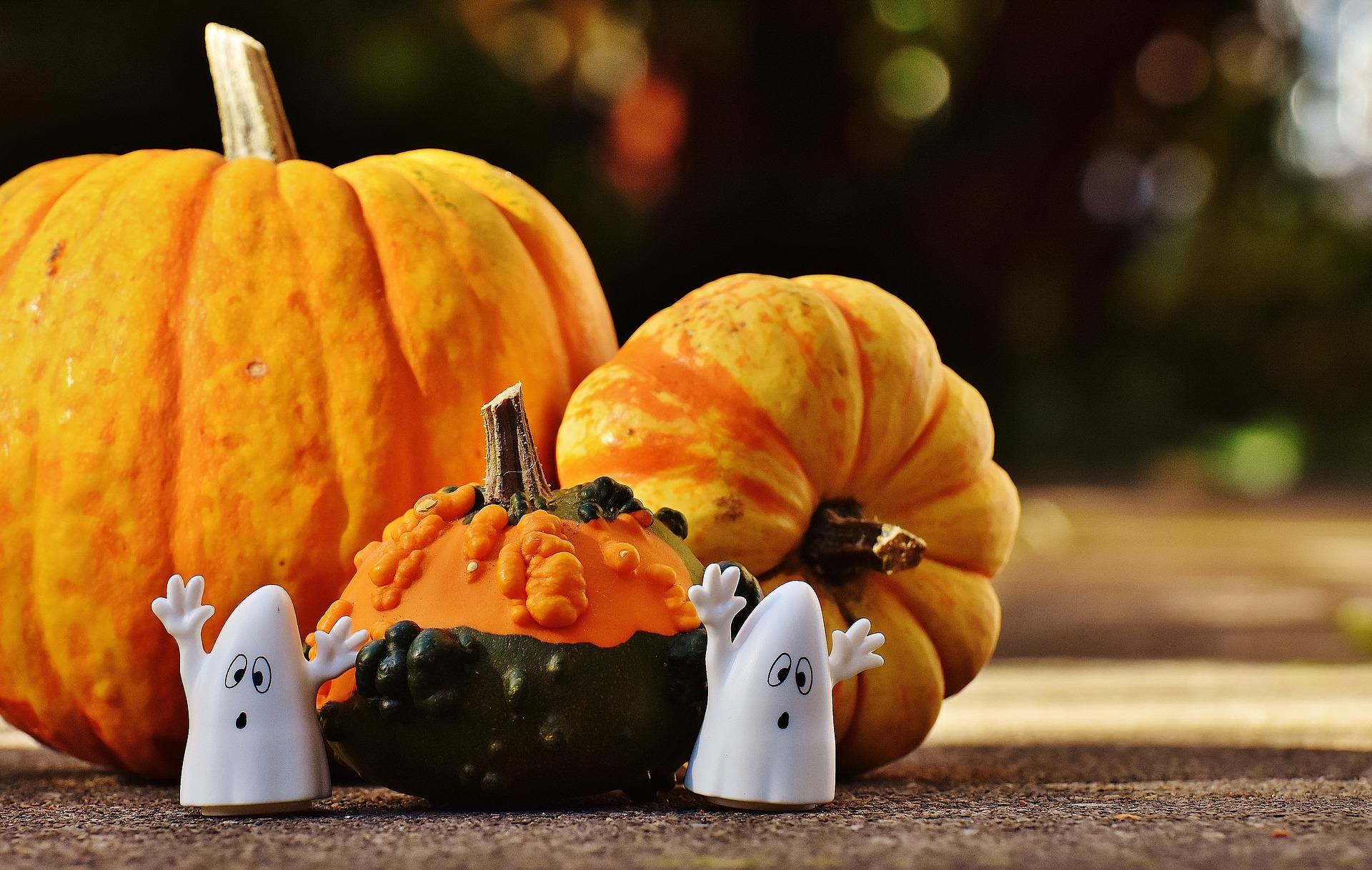 Picture of toy ghosts standing next to pumpkins.